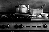 A Skillet and Tea Kettle on a Commerical Stove
