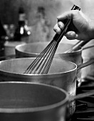 A Hand Using a Whisk in a Steaming Saucepan