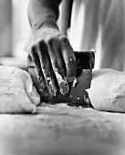 A Hand Using a Scraper with Dough