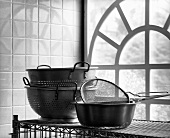 Assorted Colanders on a Rack by a Large Window