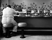 A Large Man at a Lunch Counter with a Variety of Cakes