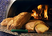 Loaves of Fresh Baked Bread Next to a Woodburning Oven