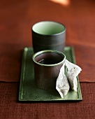 Two Handless Japanese Tea Cups on a Tray with Two White Cotton Tea Bags