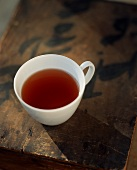 Cup of Tea in a White Tea Cup on Old Wooden Box with Asian Calligraphy