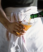 Man Wearing White Apron Pouring Beer from Bottle into Glass
