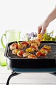 Hand Placing Shrimp and Vegetable Skewer on Table Top Grill