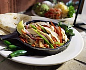 Strips of chicken & peppers in cast-iron frying pan; tortillas
