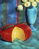 Angeschnittener Käselaib (Gouda) mit Messer