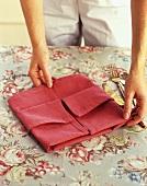 A Person Folding a Napkin