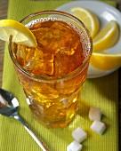 Iced tea in glass; lemon wedges; sugar cubes