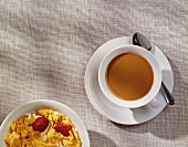 Cup of Coffee with a Bowl of Cornflakes and Strawberries