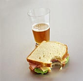 Ham and Cheese Sandwich with a Bite Taken Out; Glass of Beer
