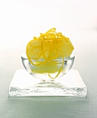 Scoops of Lemon Sorbet with Lemon Zest in a Glass Bowl; Resting on Square Glass
