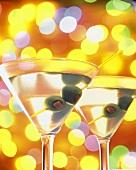Zwei Gläser Martini mit Oliven vor buntem Hintergrund