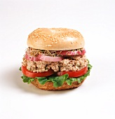 Tuna Salad Sandwich on a Bagel with Lettuce, Tomato, Onion and Sprouts; White Background