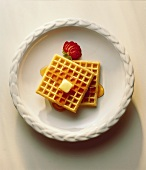 Two Waffles on a White Plate; Syrup and Butter