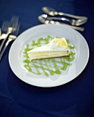 Piece of lemon tart with lime sauce on plate