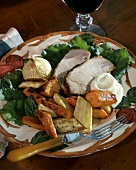 Sliced roast pork with vegetables and sour cream