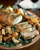 Roast pork, slices carved, with rosemary and vegetables