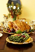 Roast Turkey on a Platter with Platter of Asparagus on Thanksgiving Table