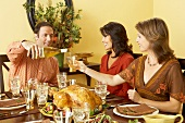 Man Pouring Wine into Woman's Glass as They are Sitting Down to Thanksgiving Meal