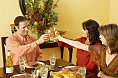 Man and Women Toasting with White Wine at Thanksgiving Table