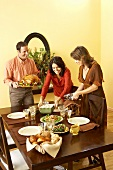 Man and Women Setting Thanksgiving Table, Man Holding Platter of Roasted Turkey