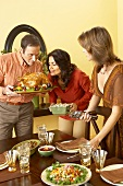 Man and Women Smelling Roasted Turkey While Setting Thanksgiving Table