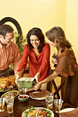 Man and Women Setting Thanksgiving Table with Prepared Meal