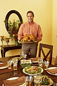 Man Holding Platter with Roasted Thanksgiving Turkey, Holiday Table