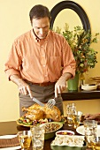 Man Standing at Dining Table Carving Thanksgiving Turkey