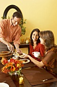 Man Serving Pie to Women at Thanksgiving Table