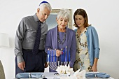 Woman with Man and Woman Lighting the Manora for Hanukkah