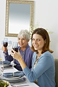 Two Women Holding Glasses of Red Wine While Sitting at Hanukkah Diner Table