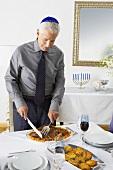 Man Slicing Brisket for Hanukkah Dinner, Wearing Yamaka