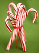 Christmas Candy Canes Bundled with Red Ribbon on a Green Background
