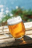 Helles Bier im Glaskrug auf Holztisch im Freien