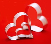 Three Assorted Sized Heart Shaped Cookie Cutters, Red Background