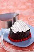 Heart Shaped Cupcake Decorated with Vanilla Frosting and Red Candies