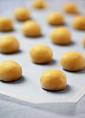 Uncooked Sugar Cookie Dough Balls on Parchment Paper