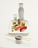 Assorted Sushi on a Square White Plate; Chopsticks with Soy Sauce; Sake