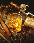 Glass of Scotch on the Rocks with Fishing Pole and Cattail on a Log