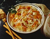 Wide Noodles and Salmon in a Bowl with Bread Sticks