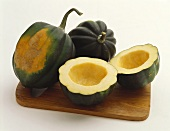 Acorn Squash on a Wooden Board: Whole and Halved