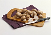 Cremini Mushrooms on a Wooden Board with Knife