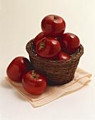 Rote Äpfel im Korb, zwei daneben