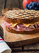 Whole Grilled Ham and Cheese Sandwich on a Cutting Board