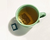 Cup of Green Tea with Tea Bag on a White Background