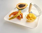 Half of a Papaya with Papaya Wedges and a Bowl of Mashed Papaya