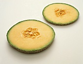 Two Slices of Cantaloupe on a White Background
